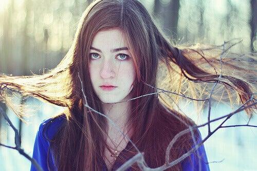 naisen hiukset ovat tarttuneet puun oksiin