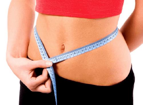 nainen mittaa vyötäröä
