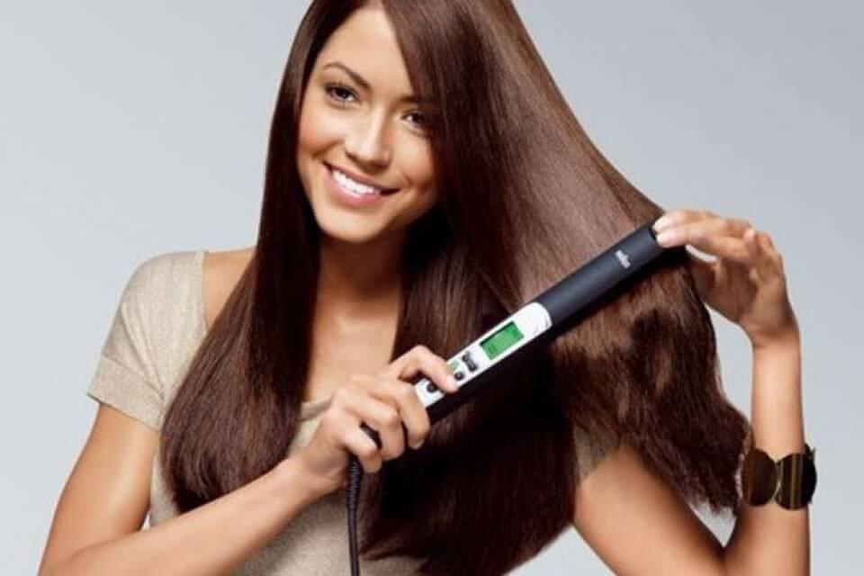nainen suoristaa hiuksia