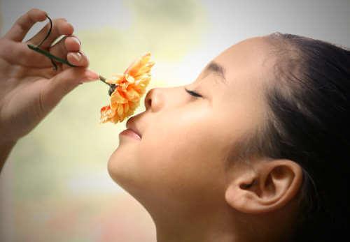 tyttö haistelee kukkaa