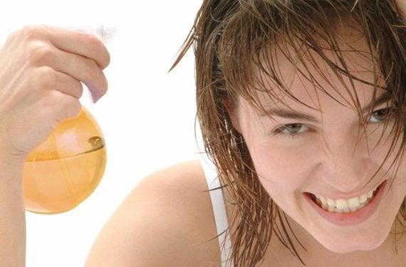 Nainen suihkuttaa hiuksiaan