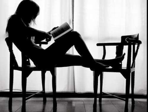 Nainen lukee tuolilla
