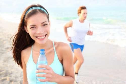Urheilija rannalla vesipullo kädessä