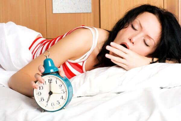 Nainen haukottelee aamulla sängyssä