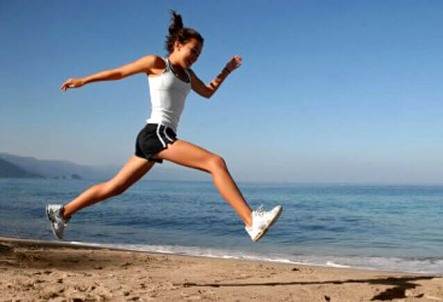 Nainen hyppii rannalla