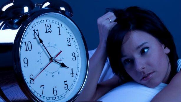 Nainen katsoo herätyskelloa