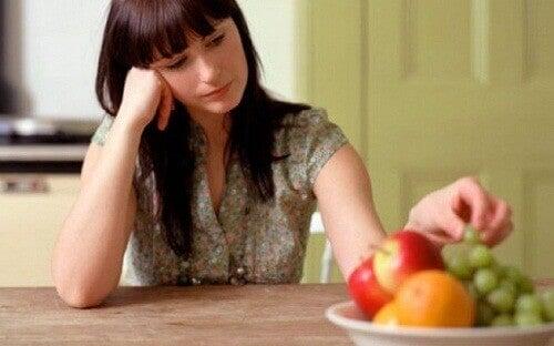 Nainen nyppii hedelmiä