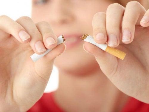 Nainen katkaisee tupakan