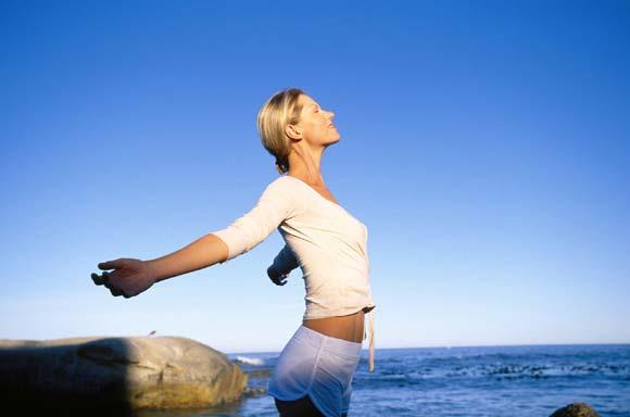 Nainen nauttii meri-ilmasta