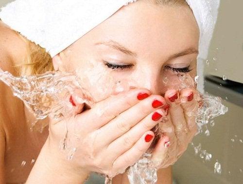 Nainen peseee kasvot