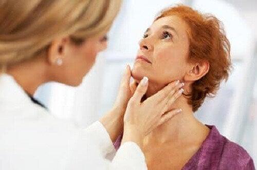Lääkäri tunnustelee potilaan kaulaa