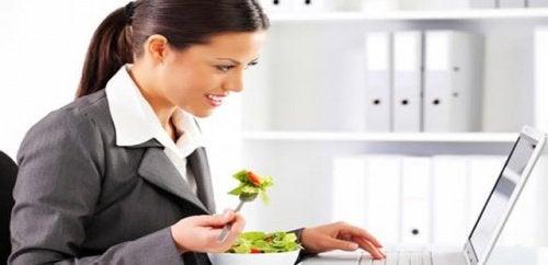 Nainen syö salaattia töissä