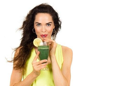 Nainen juo vihreää mehua