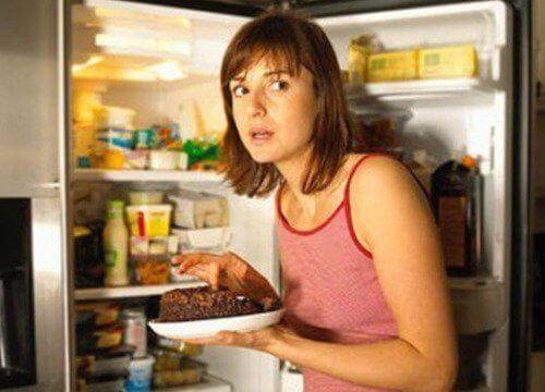 Ruoanhimo ja nainen jääkaapilla