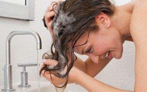 nainen pesee hiuksiaan