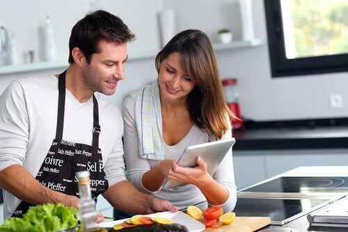 pariskuntaa tekee ruokaa yhdessä