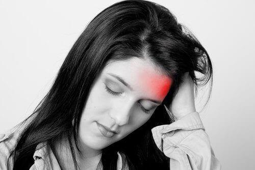 naisen ohimoita särkee