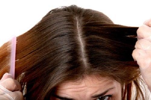 nainen kampaa hiuksiaan