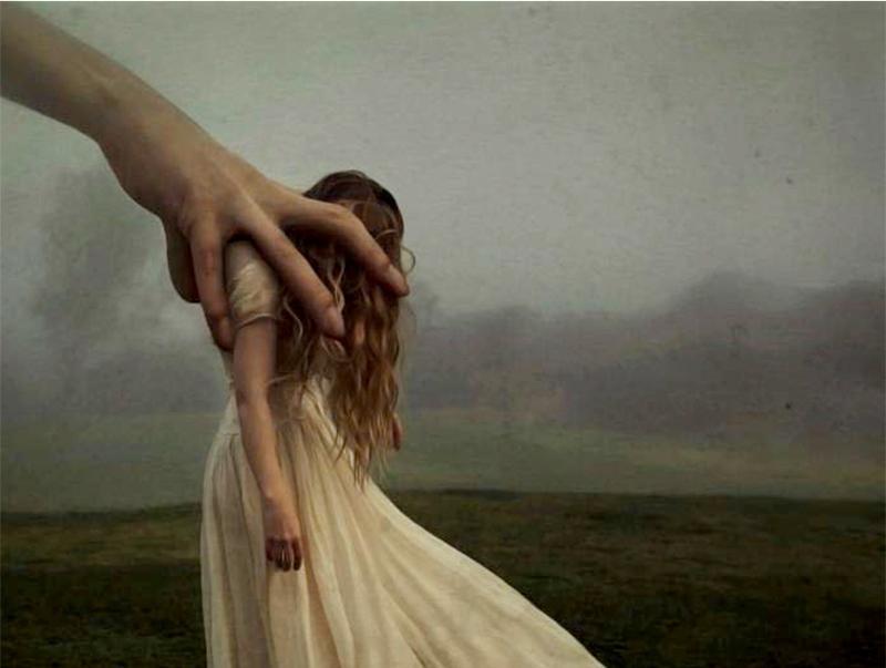 suuri käsi riepottelee naista