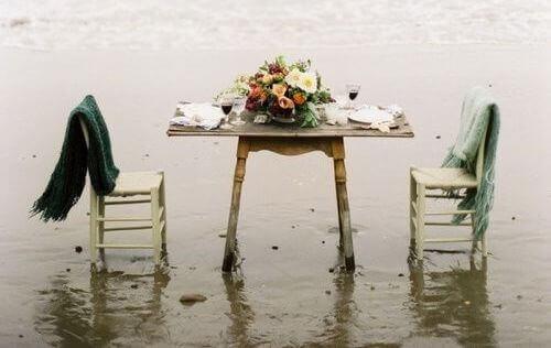 rantavedessä on pöytä ja tyhjät tuolit