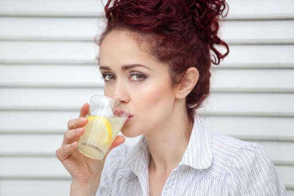 nainen juo sitruunavettä