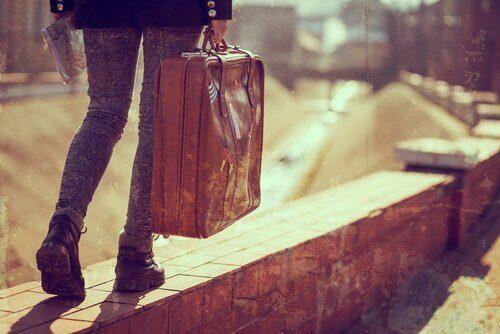 nuori ihminen kantaa matkalaukkua