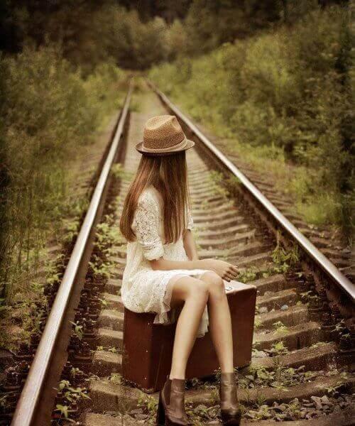 tyttö istuu autiolla raiteella