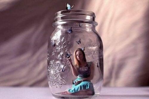 tyttö istuu lasipurkissa