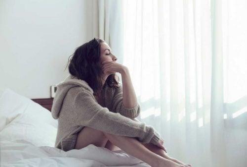 nainen pohtii sängyllä