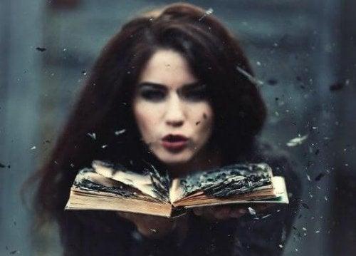 nainen puhaltaa poltettua kirjaa