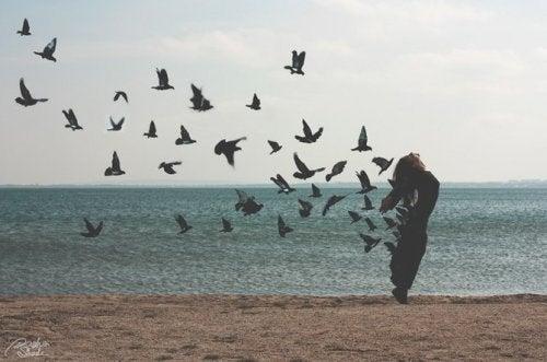 nainen ja linnut rannalla