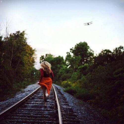 nainen juoksee rautatiellä