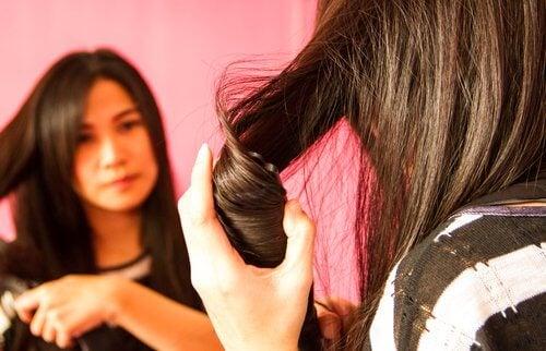 nainen kihartaa hiuksiaan