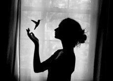 nainen ja kolibri ikkunan edessä