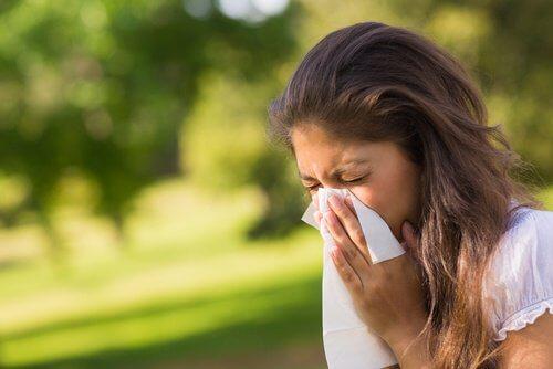 nainen niistää sillä hänellä on allergiaa