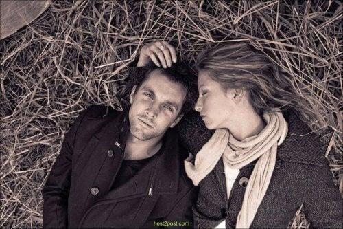 surullinen pariskunta makaa heinillä