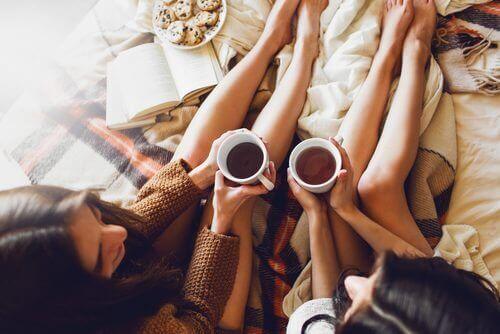 ystävykset juovat teetä sängyssä