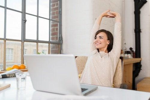 nainen venyttelee tietokoneen edessä