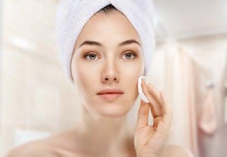 nainen puhdistaa kasvonsa