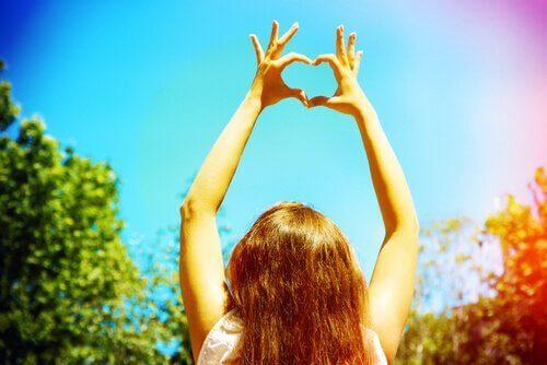 muodostaa sydämen sormillaan