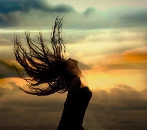 nainen heilauttaa hiukset taakse
