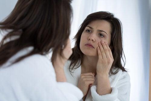 nainen tutkii kasvojaan peilistä