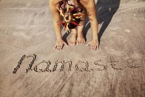 nainen kirjoitti hiekkaan namaste