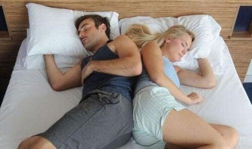 pari nukkuu selät vastakkain