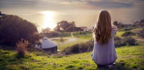 nainen istuu kukkulalla