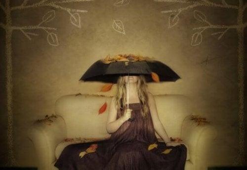 nainen sohvalla sateenvarjon alla