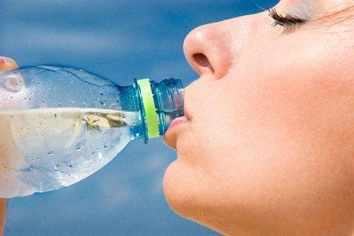 nainen juo vettä pullosta