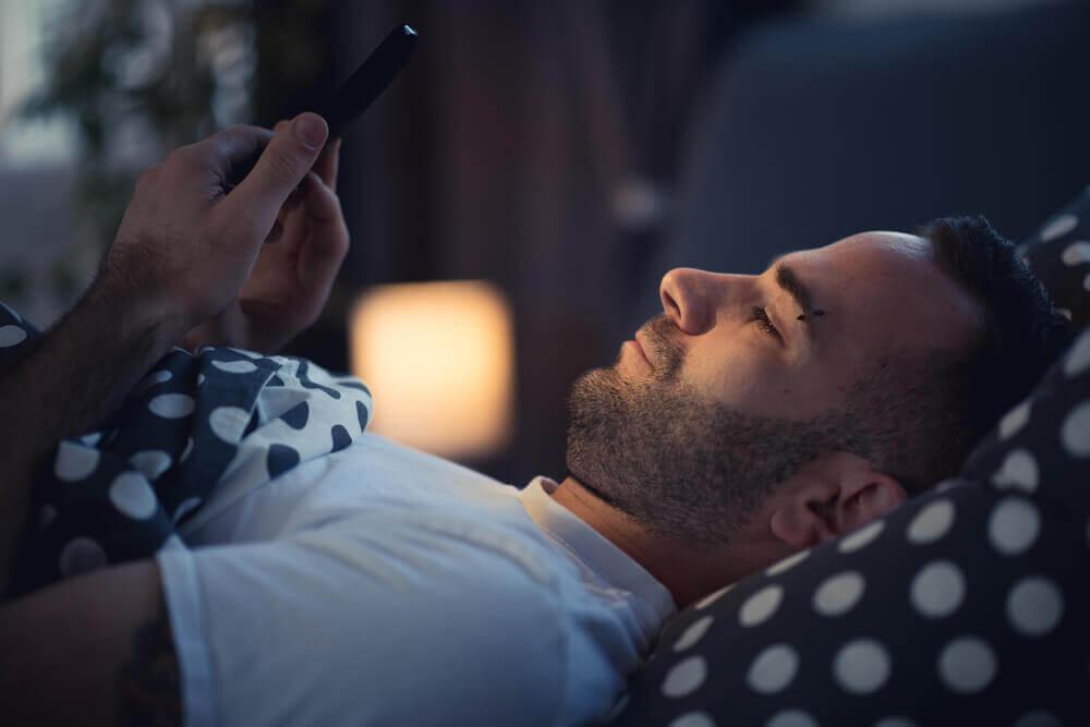 mies tekstaa sängyssä