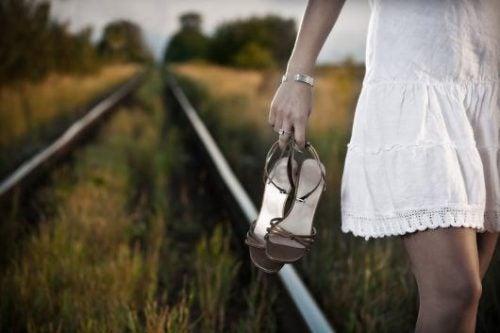 nainen kävelee rautatiellä ilman kenkiä