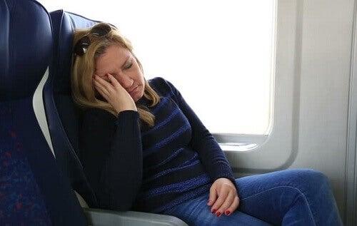 nainen yrittää nukkua lentokoneessa